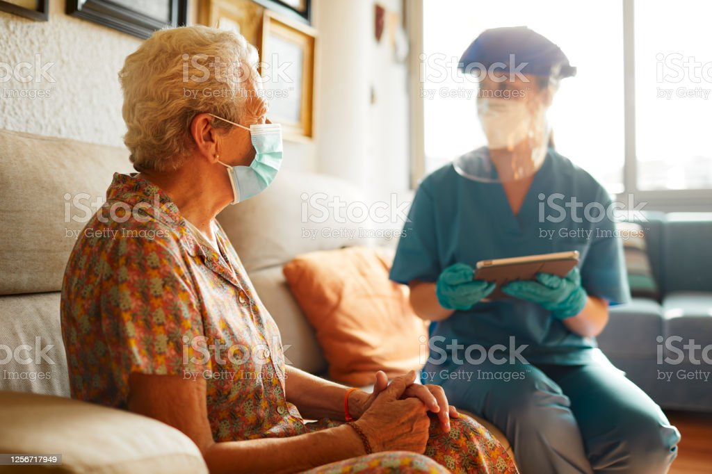 A female doctor visits a senior woman at the nursing home. Testing covid at home 70-79 Years Stock Photo