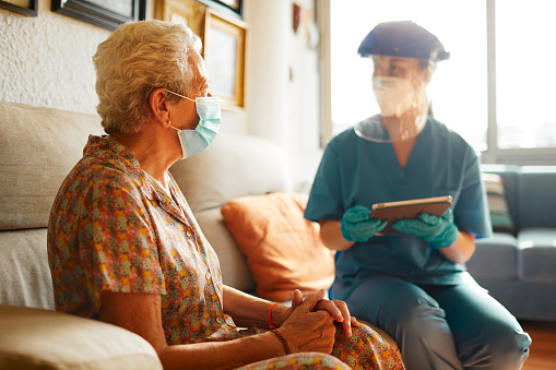 A Female Doctor Visits A Senior Woman At The Nursing Home Stock Photo - Download Image Now