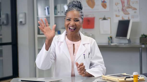 female doctor waves at camera during web conference - sventolare la mano foto e immagini stock