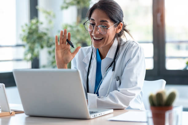 Female doctor waving and talking with colleagues through a video call with a laptop in the consultation. Shot of female doctor waving and talking with colleagues through a video call with a laptop in the consultation. physician stock pictures, royalty-free photos & images