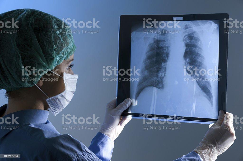 Female doctor wearing a mask looking at X-ray stok fotoğrafı