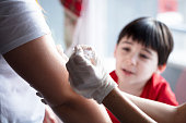 istock female doctor wearing latex gloves injecting a child's mom in her arm with a needle and syringe containing a dose of the COVID-19 vaccine cure by way of immunisation 1322195845