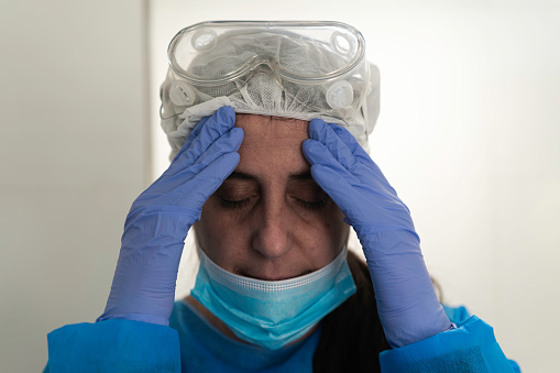 Female doctor wearing protective clothes, worried