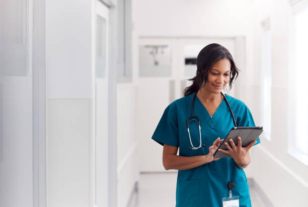 Female Doctor Wearing Scrubs In Hospital Corridor Using Digital Tablet Female Doctor Wearing Scrubs In Hospital Corridor Using Digital Tablet ipad stock pictures, royalty-free photos & images