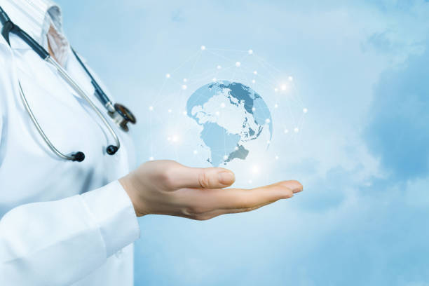 A female doctor with a stethoscope on her neck is holding a crystal, sparkling global map on her hand . stock photo