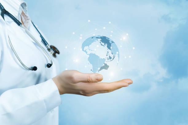 Eine Ärztin mit einem Stethoskop am Hals hält ein Kristalls, funkelnde Weltkarte auf der Hand. – Foto