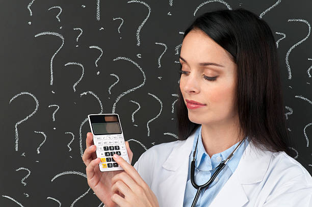 female doctor with calculator in front of question marks - question mark asking doctor nurse stock photos and pictures