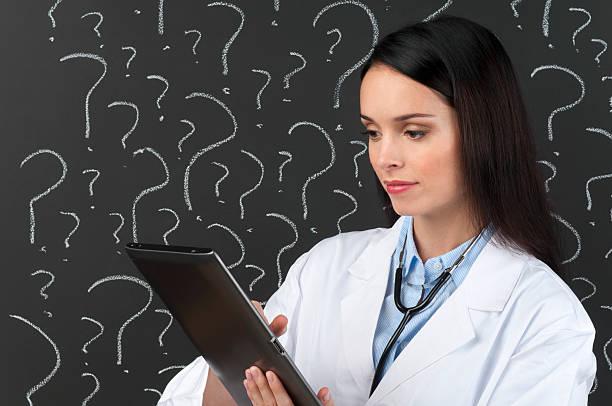 female doctor with digital tablet in front of question marks - question mark asking doctor nurse stock photos and pictures