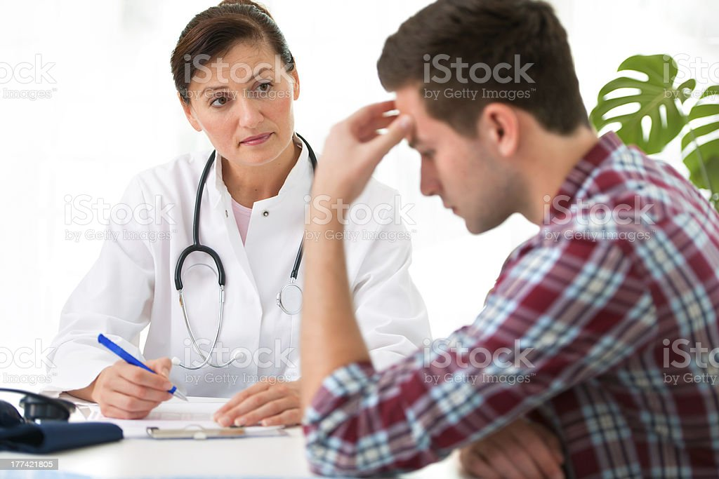 Female doctor with male patient who is holding his head royalty-free stock photo