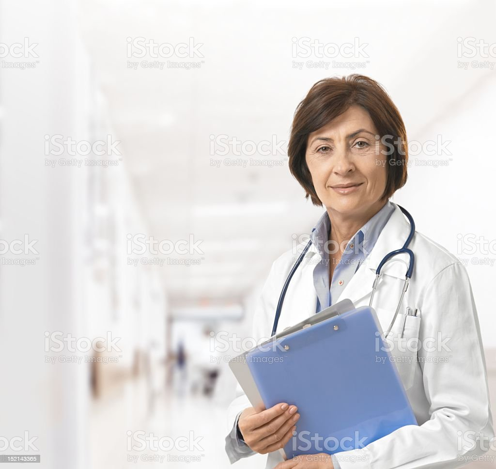 A female doctor with medical charts in a hospital corridor royalty-free stock photo