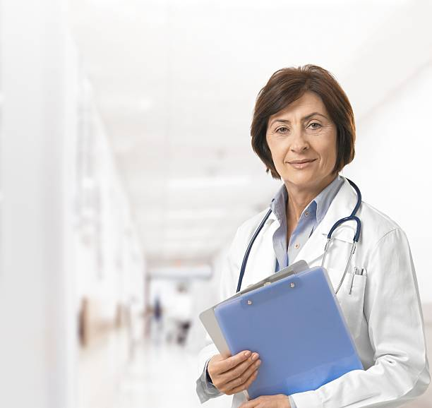 A female doctor with medical charts in a hospital corridor stock photo