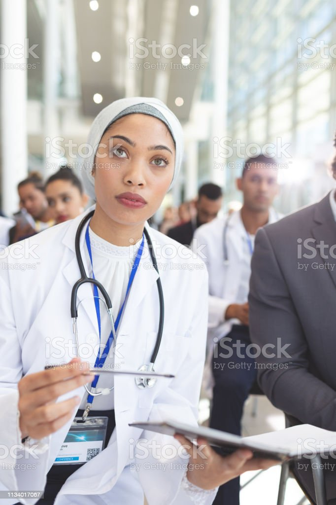 Front view of mixed race female doctor with notebook and pen...