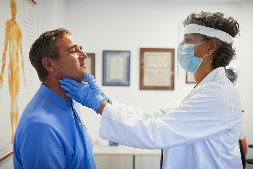 A female doctor with protective work wear doing a  thyroid gland control.