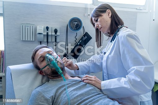 871683804istockphoto Female doctor with sick man patient with Oxygen Mask in hospital emergency room. In Smoking and respiratory diseases and anti tobacco advertising campaign. 1185868951