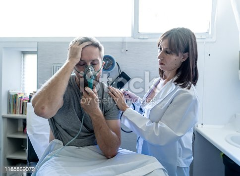 871683804istockphoto Female doctor with sick man patient with Oxygen Mask in hospital emergency room. In Smoking and respiratory diseases and anti tobacco advertising campaign. 1185869072