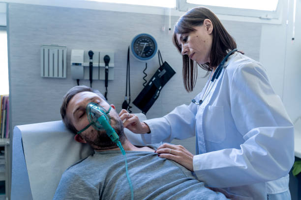 female doctor with sick man patient with oxygen mask in hospital emergency room. in lung cancer, smoke inahlation and respiratory or infectious diseases and virus outbreaking concept. - infezione respiratoria foto e immagini stock
