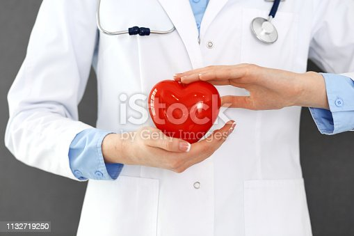 istock Female doctor with stethoscope holding heart in her arms. Healthcare and cardiology concept  in medicine 1132719250