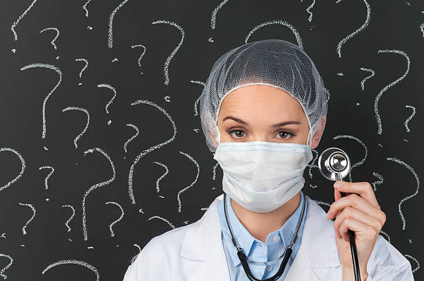 female doctor with stethoscope in front of question marks - question mark asking doctor nurse stock photos and pictures