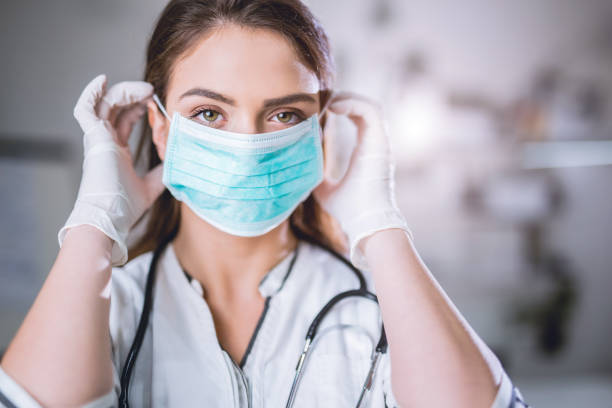 Female doctor with surgical mask on Young medical professional with procedure mask on her face disposable stock pictures, royalty-free photos & images