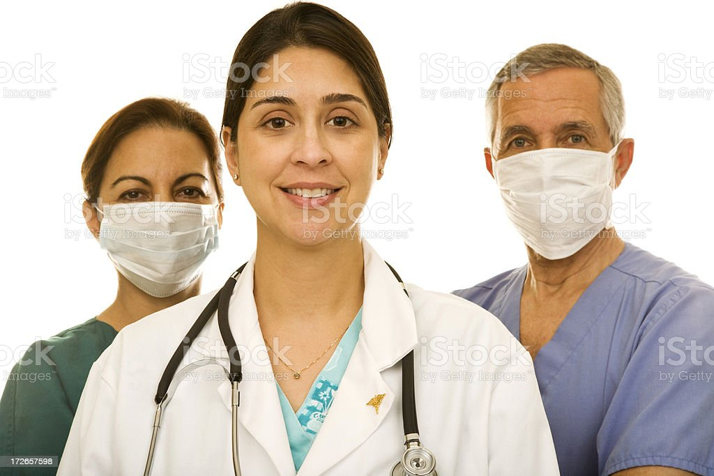 Female doctor with two surgeons wearing masks royalty-free stock photo