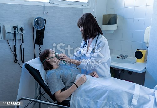 871683804istockphoto Female doctor with young sick woman patient with Oxygen Mask looking in pain and worried in hospital. In Health care, Smoking and respiratory diseases and anti tobacco advertising campaign. 1185868931