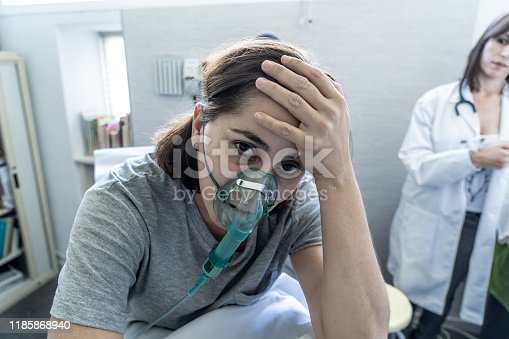 871683804istockphoto Female doctor with young sick woman patient with Oxygen Mask looking in pain and worried in hospital. In Health care, Smoking and respiratory diseases and anti tobacco advertising campaign. 1185868940