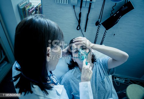 871683804istockphoto Female doctor with young sick woman patient with Oxygen Mask looking in pain and worried in hospital. In Health care, Smoking and respiratory diseases and anti tobacco advertising campaign. 1185868992