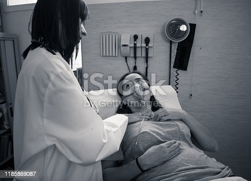871683804istockphoto Female doctor with young sick woman patient with Oxygen Mask looking in pain and worried in hospital. In Health care, Smoking and respiratory diseases and anti tobacco advertising campaign. 1185869087