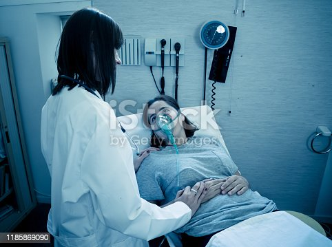 871683804istockphoto Female doctor with young sick woman patient with Oxygen Mask looking in pain and worried in hospital. In Health care, Smoking and respiratory diseases and anti tobacco advertising campaign. 1185869090
