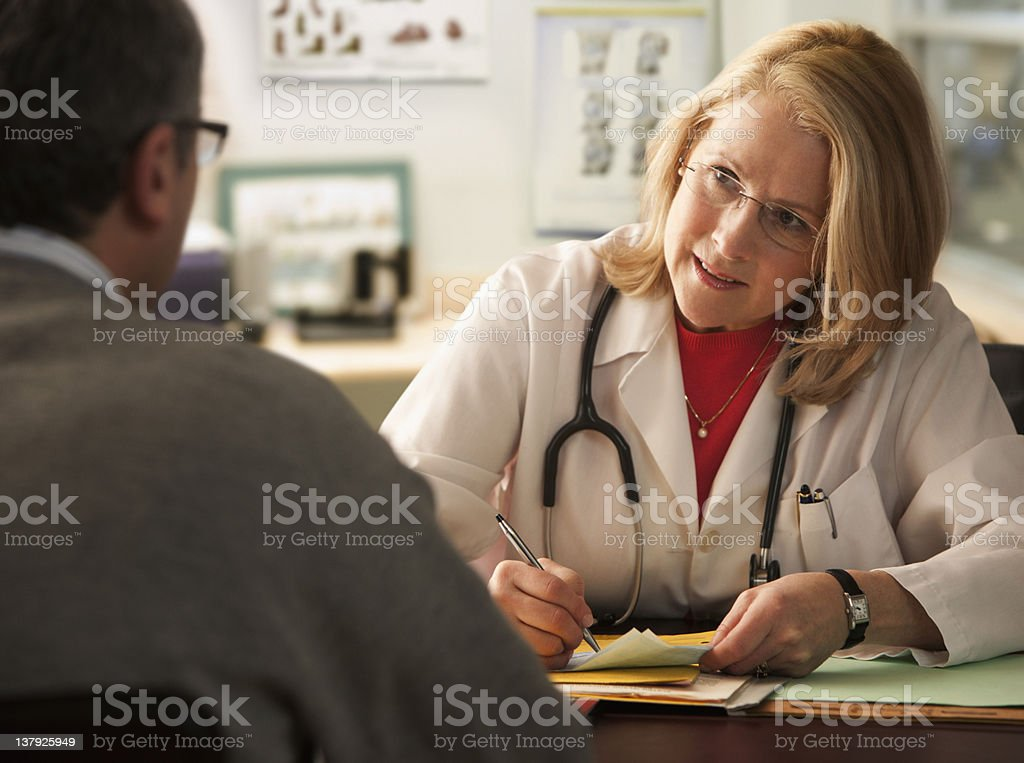 Female Doctor writing notes on male patient royalty-free stock photo
