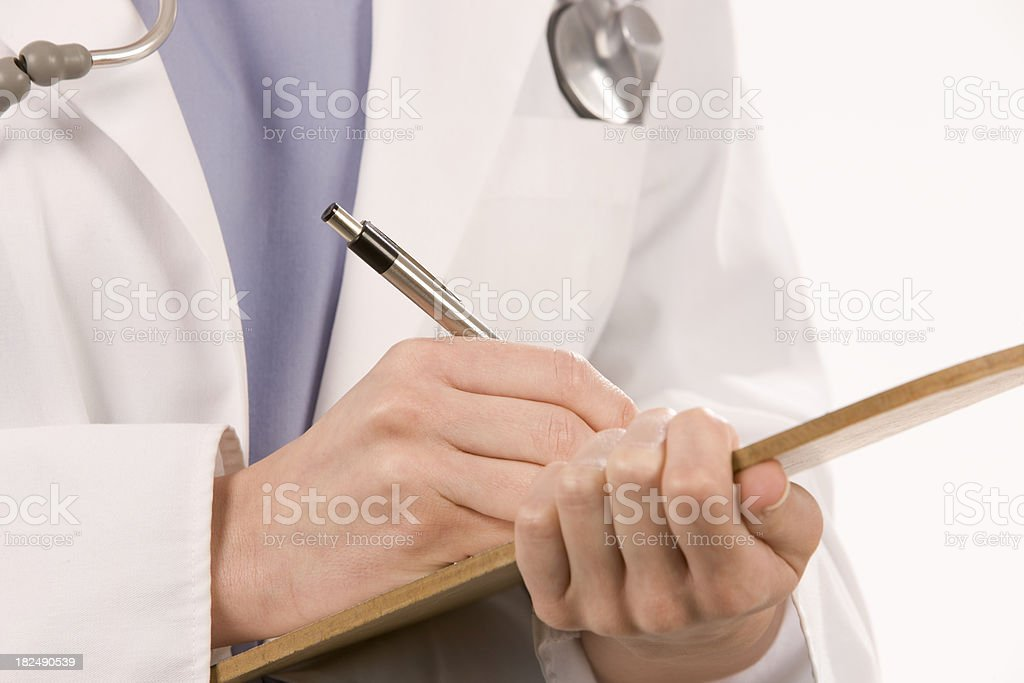 Female Doctor writing on clipboard royalty-free stock photo