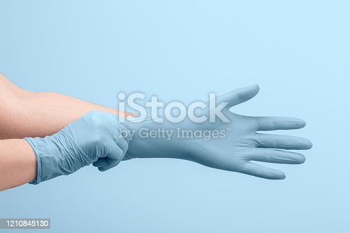 Female doctor's hands putting on white sterilized surgical gloves