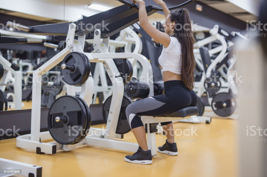 Female doing exercies on sports machine in gym stock photo