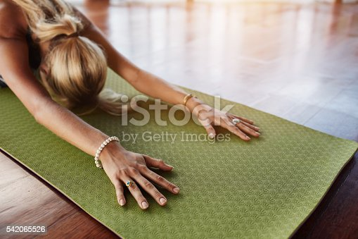 istock Female doing stretching workout on exercise mat 542065526