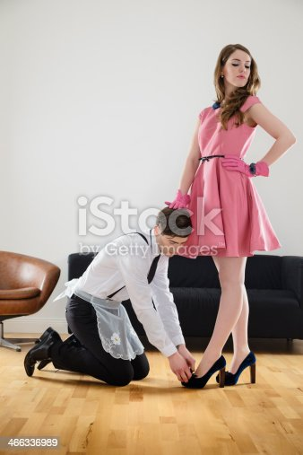 1960s style retro couple in a female dominance situation. Man is on his knees cleaning the shoes of the female. Vertical shot.
