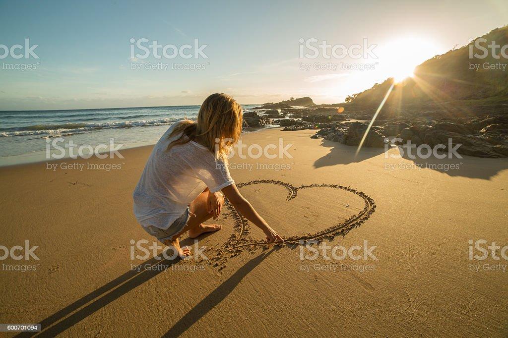 Female drawing heart shape on beach stock photo