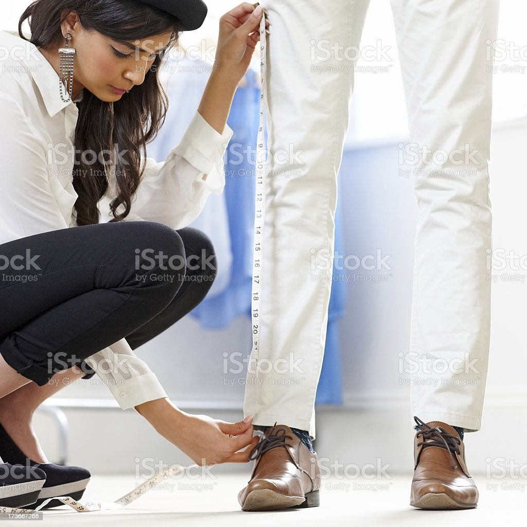 Female dressmaker measuring height of a man in fashion studio stock photo