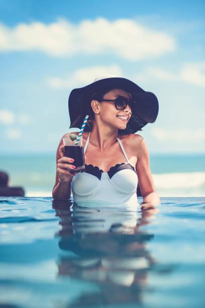 weibliche cocktail trinken und sonnenuntergang im infinity-pool - traum pools stock-fotos und bilder