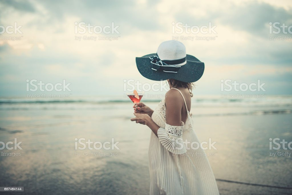 Female Drinking Cocktail and Enjoying the Sunset Ocean View stock photo
