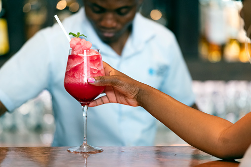 Female drinking strawberry daiquiri at bar