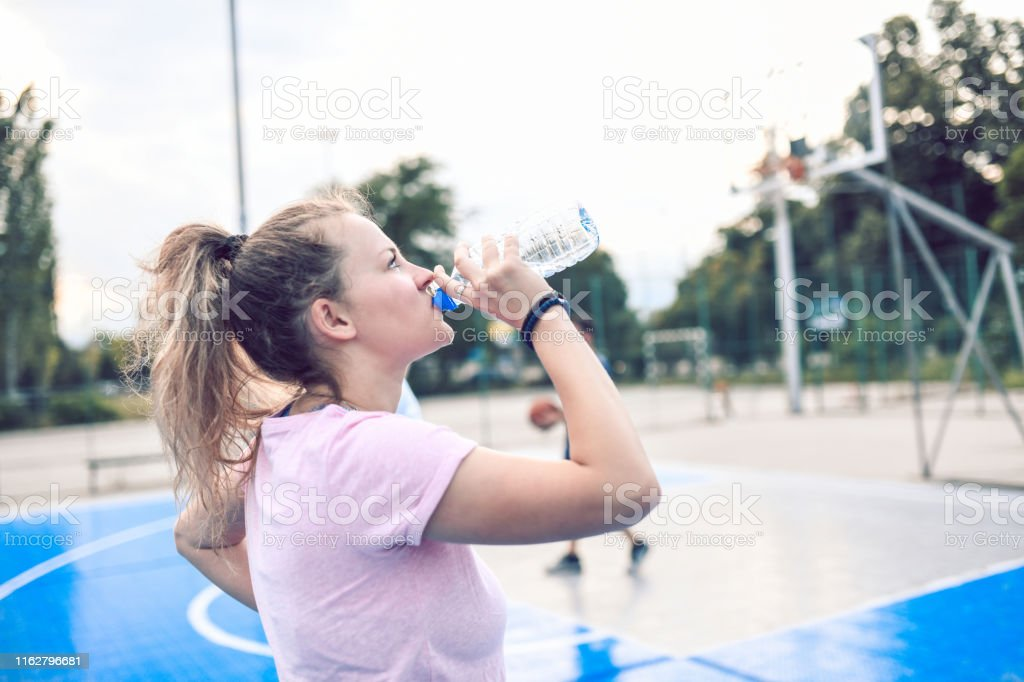 Female Drinking Water During Basketball Training