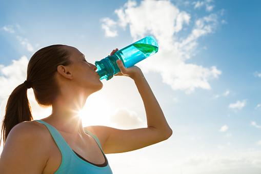 Female drinking a fresh water from bottle.