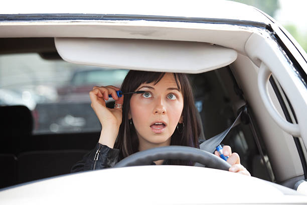 female driver distracted while applying mascara - detraction stock pictures, royalty-free photos & images
