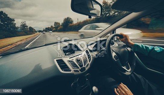 A female driver driving a car along a busy road on an English single carriageway on a cloudy overcaste day. Filter and styling applied.