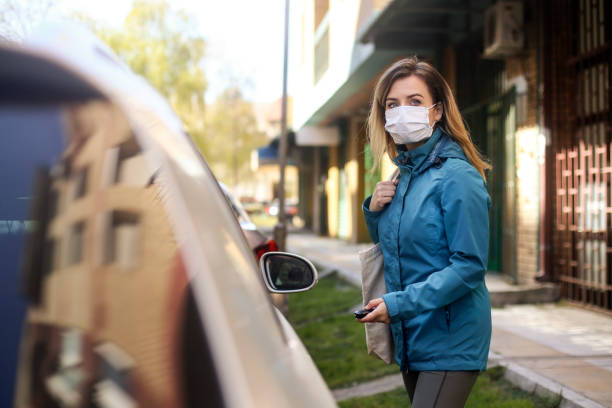 Female driver entering her car during the pandemic stock photo