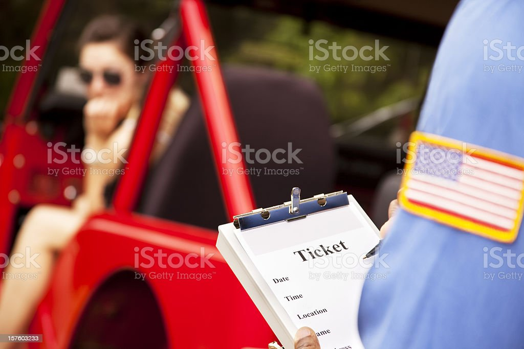 Female driver in red vehicle getting traffic ticket from policeman. stock photo