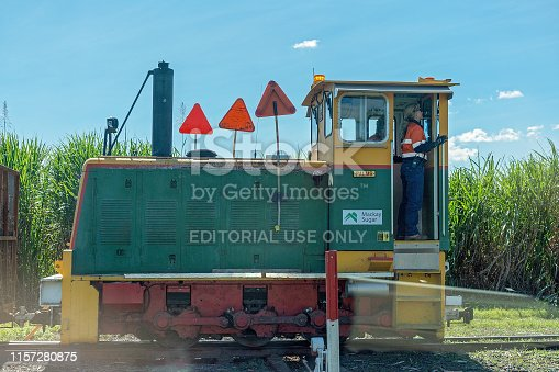 Mackay, Queensland, Australia - June 2019: A female locomotive driver at work carting harvested sugar cane to the refinery mill