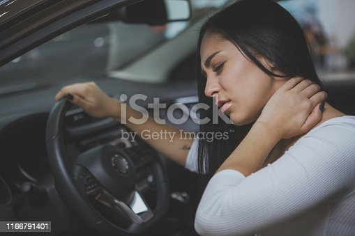 Beautiful young woman rubbing her neck, feeling sore after long drive. Female driver having terrible neck pain after whiplash injury in car crash. Healthcare, safety, pain concept