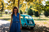 istock Female driver walking near vintage car 1175729103