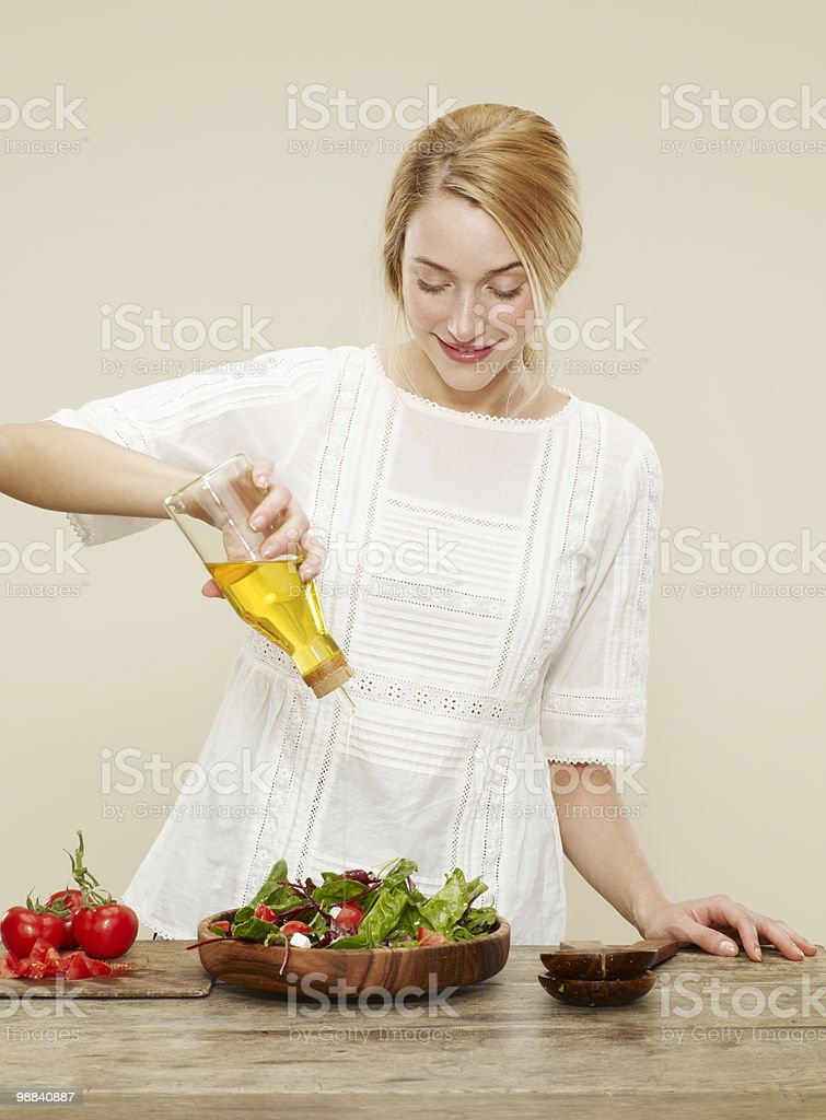 female drizzling olive oil over salad royalty free stockfoto